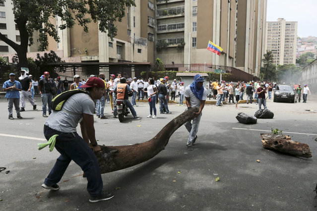 Opposition members set up a barricade during a protest in Caracas, Venezuela, Wednesday, April 19, 2017. (Photo by Fernando Llano/AP Photo)
