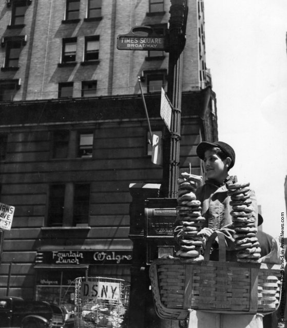 1947:  A pretzel vendor selling his wares from a wicker basket in the Times Square and Broadway area of New York
