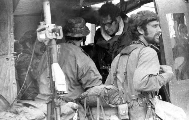 Four Vietnam War photojournalists are seen waiting for a helicopter flight into Laos to cover South Vietnamese forces attacking the Ho Chi Minh Trail on February 10, 1971. From left (inside helicopter): Keisaburo Shimamoto, Newsweek; Henri Huet, AP (back to camera); Larry Burrows, Life magazine; and Kent Potter, United Press International (standing at right). All four were killed in 1971 when the helicopter they were flying in was shot down. (Photo by Sergio Ortiz/AP Photo)