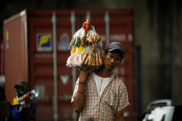 A street vendor carries snacks for sale at the street in Jakarta, Indonesia, March 30, 2016. (Photo by Reuters/Beawiharta)