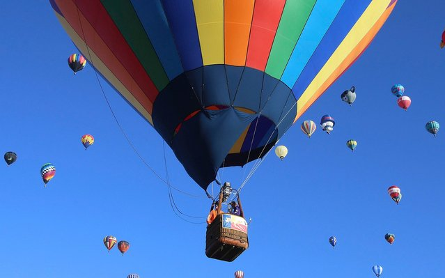 Hot air balloons fly over Albuquerque, N.M., at the Albuquerque International Balloon Fiesta Sunday, October 6, 2019. (Photo by Jerry Larson/Waco Tribune-Herald via AP Photo)