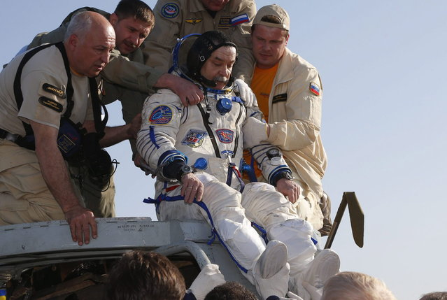 Russian space agency rescue team help Russian cosmonaut Mikhail Tyurin to get off the capsule of the Russian Soyuz TMA-11 module shortly after the landing, about 150 km (93 miles) southeast of the Kazakh town of Dzhezkazgan, Kazakhstan, Wednesday, May 14, 2014. The Soyuz space capsule carrying three astronauts who had spent a half-year aboard the International Space Station landed Wednesday in the steppes of Kazakhstan. (Photo by Dmitry Lovetsky/AP Photo)