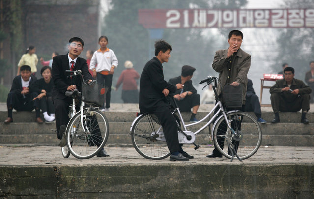 North Koreans watch from the banks of the Yalu River at the North Korean town of Sinuiju as a Chinese tour boat passes by October 10, 2006. (Photo by Reinhard Krause/Reuters)