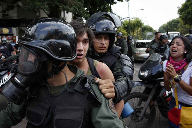 Venezuela's national guards detain an anti-government protester during a protest against President Nicolas Maduro's government in Caracas May 12, 2014. (Photo by Carlos Garcia/Reuters)
