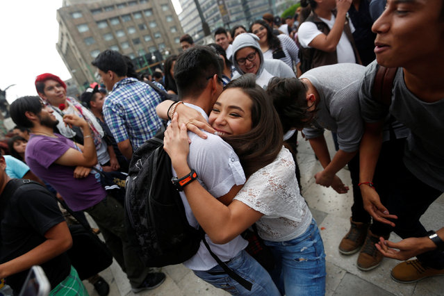 A couple embraces during a Kissathon to celebrate International Day Against Homophobia outside Bellas Artes museum in Mexico City, Mexico, May 17, 2016. (Photo by Edgard Garrido/Reuters)