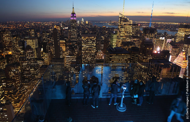 The Empire State Building towers over the Manhattan skyline as tourists gather on the observation deck of Rockefeller Center