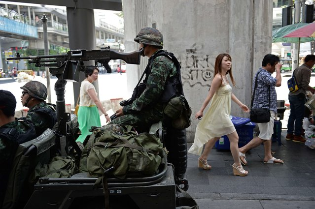 "People walk past Thai army soldiers sitting in a jeep mounted with a machine gun as they secure a main intersection in Bangkok on May 20, 2014. Thailand's army declared martial law across the deeply divided kingdom on May 20 to restore order after months of deadly anti-government protests, deploying armed troops in the capital but insisting the move was ""not a coup"". (Photo by Christophe Archambault/AFP Photo)"