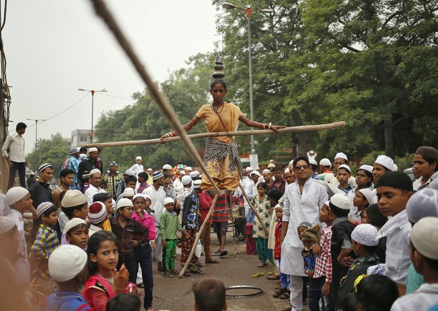 A tightrope walker performs while holding a balancing pole on the occasion of Eid al-Fitr in New Delhi, India, July 18, 2015. (Photo by Anindito Mukherjee/Reuters)