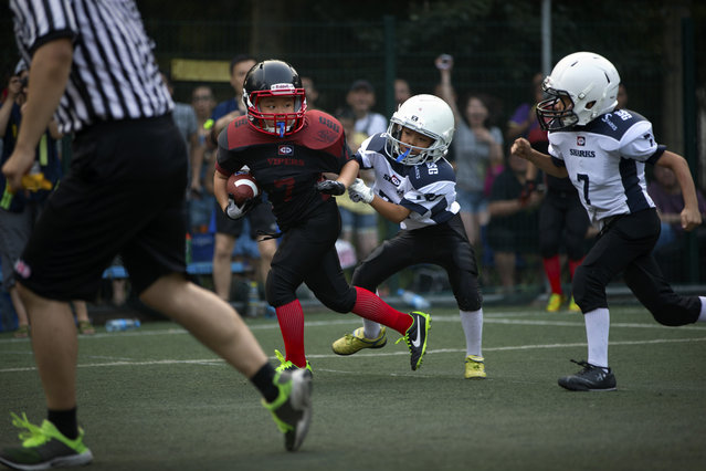 In this Sunday, July 5, 2015 photo, a young player dodges a pair of opposing tacklers during their American football game in Beijing. (Photo by Mark Schiefelbein/AP Photo)