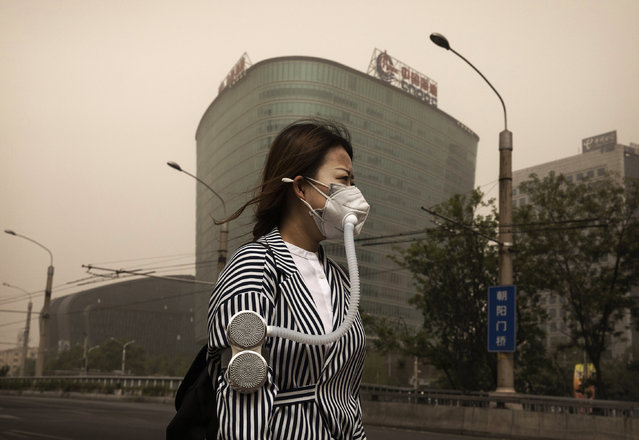 A Chinese woman wears a mask to protect from particles blown in during a sandstorm as she walks in the street on May 4, 2017 in Beijing, China. Sandstorms are common in northern China during the spring season and are caused when heavy winds from Mongolia in the north brings sand and pollutants that can blanket Chinese cities and cause air quality to deteriorate. (Photo by Kevin Frayer/Getty Images)