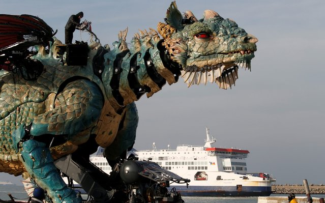 "People gather to watch ""The dragon of Calais"" performance by ""La Machine"" company,  on October 30, 2019 in Calais, northern France. Spitting fire, water and smoke, a gigantic dragon ""from another world"" will enter Calais on November 1, 2019: 10 metres high, 25 metres long, the expected mechanical monster imagined by François Delaroziere will be at the centre of a three-day ""urban show"", before becoming a tourist attraction. (Photo by Pascal Rossignol/Reuters)"