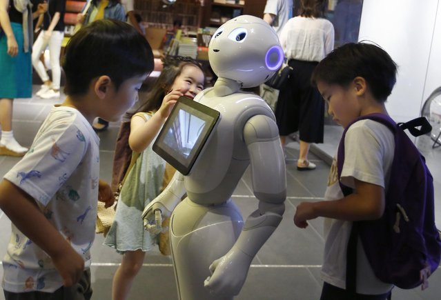 In this photo taken Sunday, July 12, 2015, children surround SoftBank Corp.'s new companion robot Pepper at a store in Tokyo. Pepper, the 121-centimeter (four-foot) tall white machine-on-wheels, offers ardent attention, cool dance moves, and small talk. Pepper has cameras, lasers and infrared in its hairless head so it can detect human faces. (Photo by Shizuo Kambayashi/AP Photo)