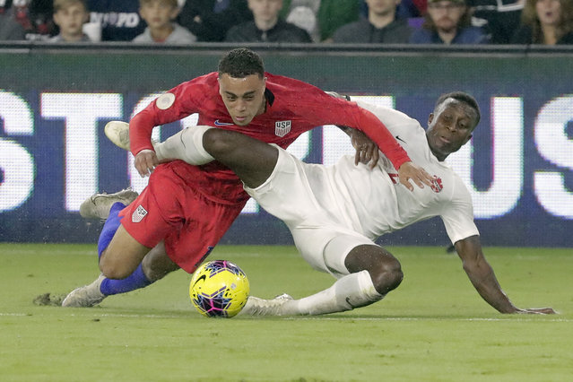 U.S. defender Sergino Dest, left, gets tangled up with Canada defender Richie Laryea while going after the ball during the first half of a CONCACAF Nations League soccer match Friday, November 15, 2019, in Orlando, Fla. (Photo by John Raoux/AP Photo)