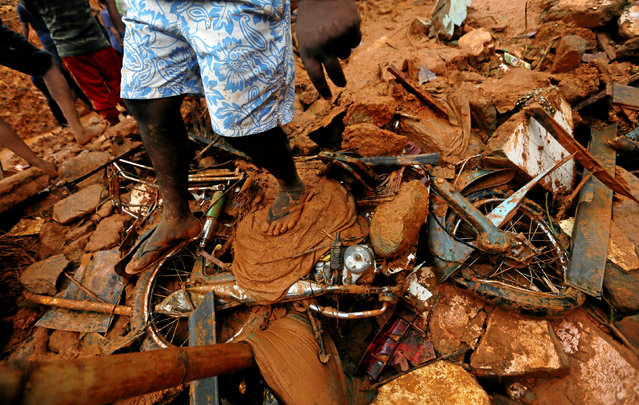 A man stands on top of a damaged bike during a rescue mission at the site of a landslide in Bellana village in Kalutara, Sri Lanka May 26, 2017. (Photo by Dinuka Liyanawatte/Reuters)