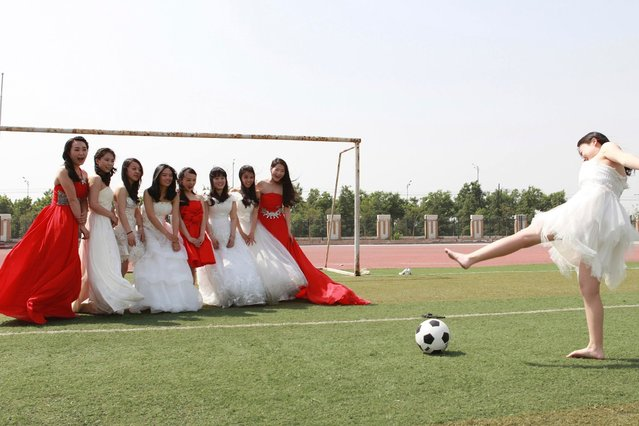College graduates pose for a photograph with a soccer ball and a goal post on a soccer field at Yuncheng University in Yuncheng, Shanxi province. (Photo by Reuters/Stringer)