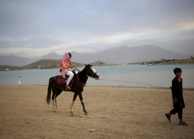 An Afghan woman enjoys a horse ride along Qargha lake, in Kabul, Afghanistan July 21, 2015. (Photo by Ahmad Masood/Reuters)