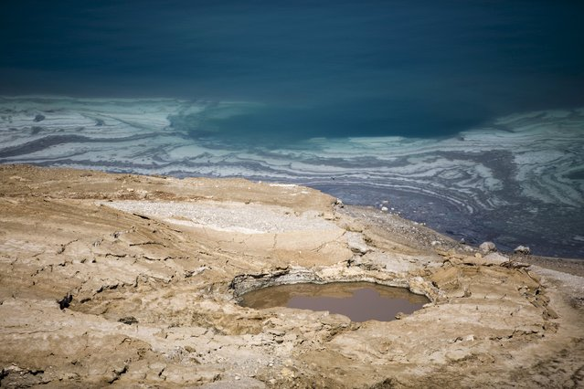 A sinkhole is seen on the shore of the Dead Sea near Kibbutz Ein Gedi, Israel July 27, 2015. The Dead Sea is shrinking, and as its waters vanish at a rate of more than one meter a year, hundreds of sinkholes, some the size of a basketball court, some two storeys deep, are devouring land where the shoreline once stood. (Photo by Amir Cohen/Reuters)
