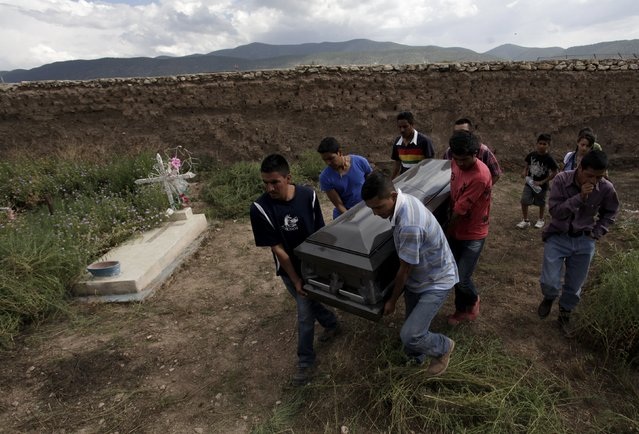 Relatives and friends carry the coffin of Luis Mendez, one of the pilgrims who died in an accident, at a cemetery in the town of Mazapil, in the Mexican state of Zacatecas, Mexico, July 30, 2015. At least 23 people were killed – including a baby – when a dump truck spun out of control after losing its brakes and hit the pilgrims in the state of Zacatecas, local media reported. (Photo by Daniel Becerril/Reuters)
