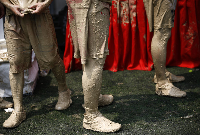 Players are covered with mud after their match at the swamp soccer China tournament in Beijing, June 26, 2014. The 32 teams from across the country participated in the soccer event to celebrate the 2014 World Cup in Brazil. (Photo by Kim Kyung-Hoon/Reuters)