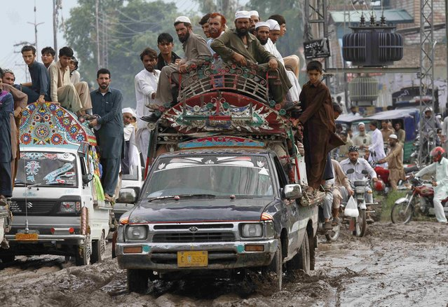 Drivers navigate muddy streets after heavy rainfall caused flooding in Peshawar, Pakistan, July 27, 2015. (Photo by Fayaz Aziz/Reuters)