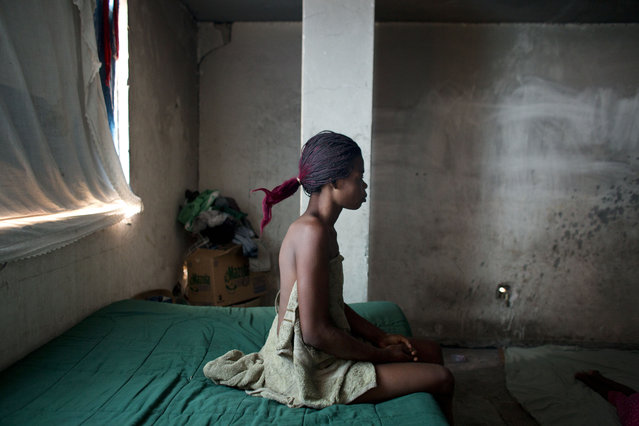 In this June 29, 2015 photo, hairdresser Loavia Bienaime, 30, sits on her bed as she prepares to begin her day in the room her family occupies in an government office building that was damaged in the 2010 earthquake in Port-au-Prince, Haiti. Bienaime's husband, Jimmy Bellefleur, used his skill as an electrician to connect the abandoned building to the power grid, and has repaired broken televisions, fans, and a blender for the family to use. (Photo by Rebecca Blackwell/AP Photo)