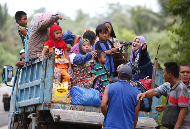 Displaced residents fleeing by a truck to safer areas stop by a roadside as government troops battle with Muslim militants Monday, May 29, 2017 in Marawi, southern Philippines. Philippine forces say they now control most of the southern city where militants linked to the Islamic State group launched a bloody siege nearly a week ago. Presidential Spokesman Ernesto Abella said Monday that only small areas of Marawi are under militants' control. (Photo by Bullit Marquez/AP Photo)