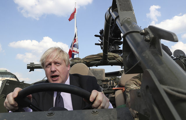 In this Thursday, June 21, 2018 file photo Britain's Foreign Secretary Boris Johnson talks to a British armed forces serviceman based in Orzysz, in northeastern Poland, during a ceremony at the Tomb of the Unknown Soldier and following talks on security with his Polish counterpart Jacek Czaputowicz in Warsaw, Poland. Boris Johnson aspires to be a modern-day Winston Churchill. Critics fear he's a British Donald Trump. Johnson won the contest to lead the governing Conservative Party on Tuesday July 23, 2019, and is set to be asked Wednesday by Queen Elizabeth II to become Britain's next prime minister. (Photo by Czarek Sokolowski/AP Photo/File)