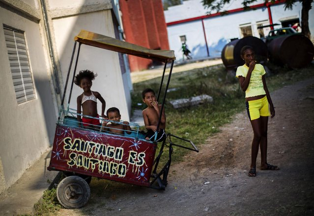 """In this March 20, 2015 photo, children pause as they play after school in an empty food cart that reads in Spanish """"Santiago is Santiago"""", parked outside their homes in Santiago, Cuba. The explosion of private enterprise is only just beginning in Santiago. Cell phones remain a rare luxury. Internet is available to the public in one state center and one hotel. (Photo by Ramon Espinosa/AP Photo)"""