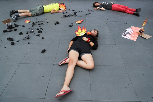 """Protesters lie on the floor during a demonstration over Australia's bushfires crisis, outside the Australian embassy in Santiago, Chile on January 10, 2020. The placard reads:""""Tell the truth"""". (Photo by Ivan Alvarado /Reuters)"""