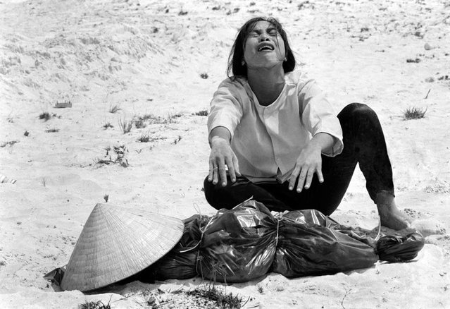 A South Vietnamese woman mourns over the body of her husband, found with 47 others in a mass grave near Hue, Vietnam in April of 1969