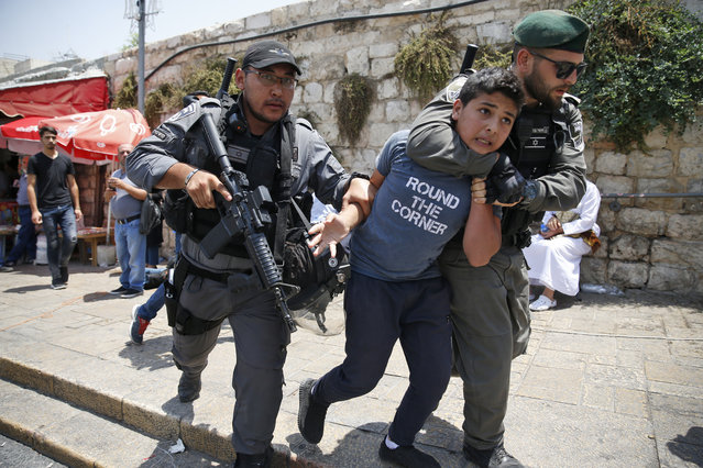 Israeli border guards detain a Palestinian youth during a demonstration outside the Lions Gate, a main entrance to Al-Aqsa mosque compound, due to newly-implemented security measures by Israeli authorities which include metal detectors and cameras, in Jerusalem's Old City on July 17, 2017. Israel reopened the ultra-sensitive holy site, after it was closed following an attack by Arab Israeli men in which two Israeli policemen were killed. (Photo by Ahmad Gharabli/AFP Photo)