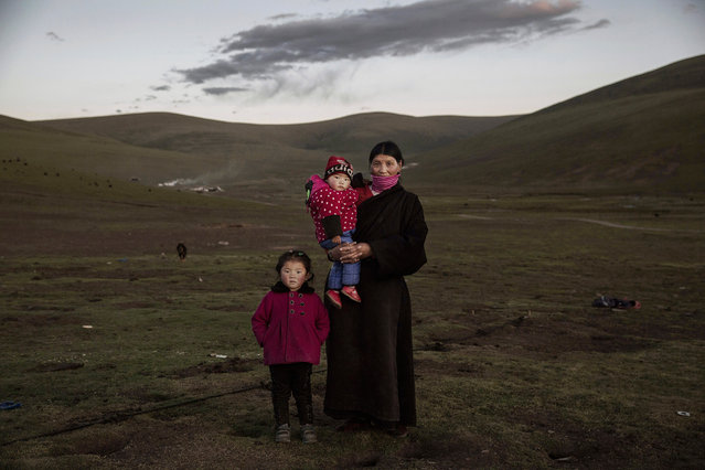 A ethnic Tibetan nomad woman stands with her grandchildren at their summer grazing area on July 24, 2015 on the Tibetan Plateau in Yushu County, Qinghai, China. (Photo by Kevin Frayer/Getty Images)