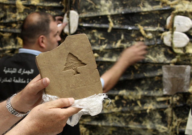 A Lebanese customs employee displays a packet of confiscated hashish stamped with a Lebanese cedar in Beirut May 27, 2009. Lebanese Internal Security forces and Lebanese Customs anti-drugs trafficking division seized a total of 85 kg (187 lbs) of hashish hidden in a refrigerated container that was supposed to be smuggled into the Netherlands. (Photo by Mohamed Azakir/Reuters)