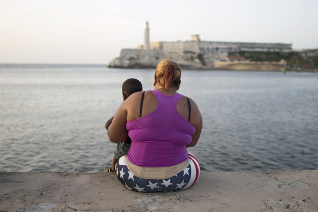 A woman who did not give her name sits with her son to watch the sunset in Havana, August 5, 2015. (Photo by Alexandre Meneghini/Reuters)
