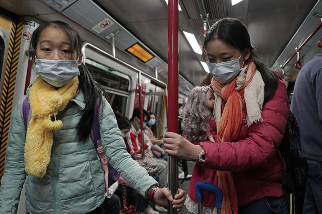 """Two girls with face masks ride the subway in Hong Kong, Saturday, February 1, 2020. China's death toll from a new virus has risen to 259 and a World Health Organization official says other governments need to prepare for""""domestic outbreak control"""" if the disease spreads. (Photo by Kin Cheung/AP Photo)"""