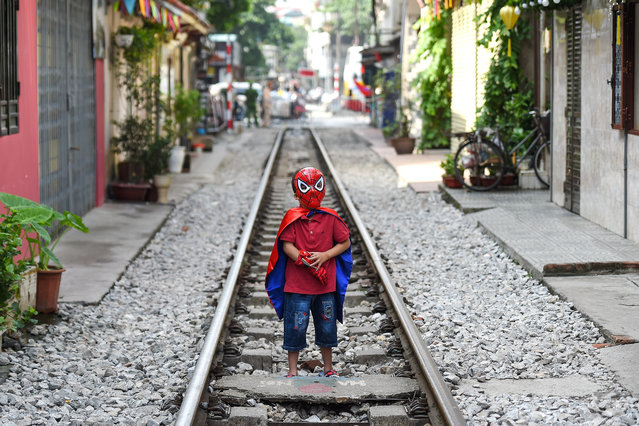 "A boy wearing a Spiderman costume stands on Hanoi's popular train street on October 10, 2019 following a municipal authorities order to deal with cafes and ""ensure safety"" on the railway track. (Photo by Nhac Nguyen/AFP Photo)"