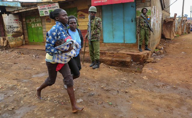 A woman carrying her child runs for safety as protesters in support of Kenyan opposition leader and presidential candidate Raila Odinga, engage in running battles with the police, in Kawangware area, Nairobi, Kenya, Thursday August 10, 2017.  International observers on Thursday urged Kenyans to be patient as they awaited final election results following opposition allegations of vote-rigging, but clashes between police and protesters again erupted in a Nairobi slum. (Photo by Brian Inganga/AP Photo)