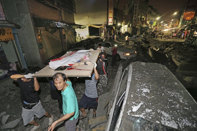 The body of a victim killed in a gas explosion from an underground gas leak is carried from the rubble in a main street in Kaohsiung, Taiwan, early Friday, August 1, 2014. A massive gas leakage early Friday caused five explosions that killed several people and injured over 200 in the southern Taiwan port city of Kaohsiung. (Photo by AP Photo)