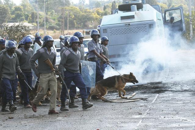 Armed Zimbabwean police battle rioters in Harare, Monday, July, 4, 2016. (Photo by Tsvangirayi Mukwazhi/AP Photo)