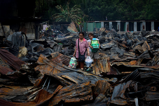 Two women carry belongings recovered from the charred remains of former homes for construction workers after a fire broke out in a housing camp in Bangkok's Don Muang district, Thailand, 07 July 2016. A large fire broke out around 10 pm local time on 06 July at a wooden housing camp for construction workers employed by Italian-Thai Development PCL, killing one young man and seriously injuring another. Initial reports indicate that the fire, which also left nearly 1,000 workers without a home, may have started due to a short circuit in one of the 700 houses. (Photo by Diego Azubel/EPA)