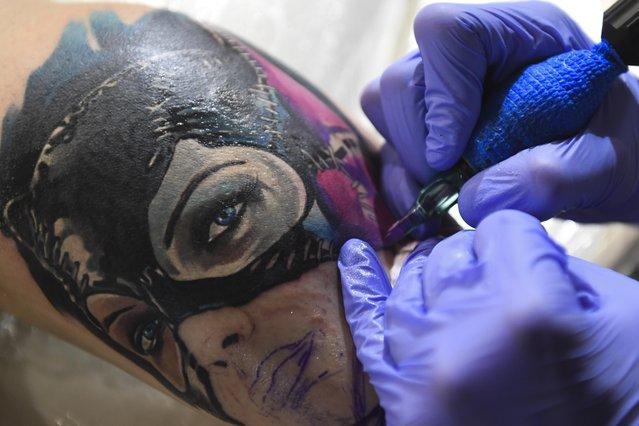 A tattoo artist applies ink during the 6th Siberian Tattoo Festival at Podzemka Loft Park in Novosibirsk, Russia on August 20, 2017. (Photo by Kirill Kukhmar/TASS)
