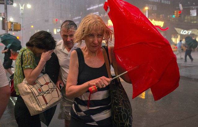 Commuters dodge high wind and heavy rain during a thunderstorm in midtown Manhattan, in New York July 18, 2012. (Photo by Adrees Latif/Reuters)