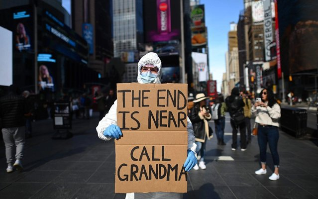 "A man wearing a hazmat suit and a mask holds a sign reading ""The end is near – call grandma"" at Times Square on March 14, 2020 in New York City. The World Health Organization said March 13, 2020 it was not yet possible to say when the COVID-19 pandemic, which has killed more than 5,000 people worldwide, will peak. ""It's impossible for us to say when this will peak globally"", Maria Van Kerkhove, who heads the WHO's emerging diseases unit, told a virtual press conference, adding that ""we hope that it is sooner rather than later"". (Photo by Johannes Eisele/AFP Photo)"