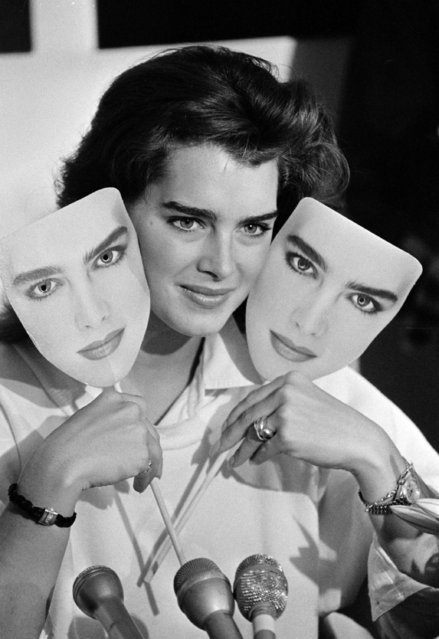 Actress-model Brooke Shields holds up two masks of her own face at the end of a press conference at a Boston department store as part of a promotional tour for a new line of clothes, August 27, 1985. (Photo by Peter Southwick/AP Photo)