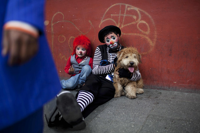 Two clowns take a rest on a sidewalk during the inauguration of the fourth annual Latin American Clown Congress in Guatemala City, Tuesday, July 24, 2012. Clowns from Central America and South America and the Caribbean have gathered for three days in the capital city to exchange ideas and attend workshops. (Photo by Rodrigo Abd/AP Photo)