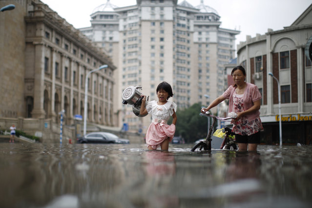 In this Wednesday, July 20, 2016 photo, a child carries kettles through a flooded street with a woman in Tianjin, China. China says dozens of people have died or gone missing since Monday in massive floods across the country's north. (Photo by Chinatopix via AP Photo)