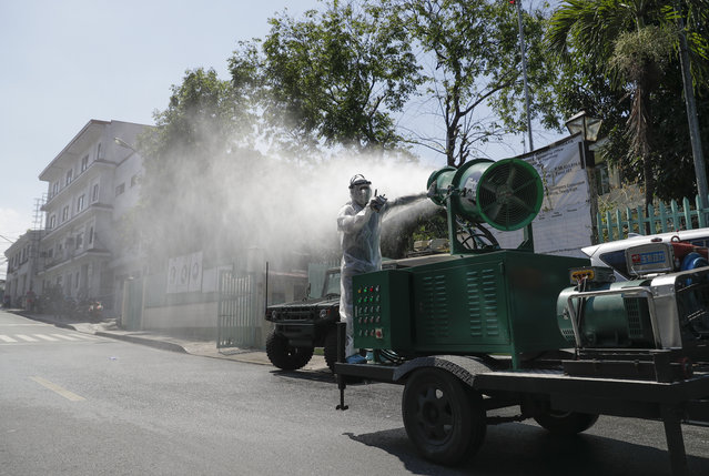 A worker in a protective suit controls a big disinfectant spray machine as they sanitize a school which has suspended classes as a precautionary measure against the new coronavirus in San Juan city in Manila, Philippines on Monday, March 9, 2020. Philippine President Rodrigo Duterte has declared a state of public health emergency throughout the country after health officials confirmed over the weekend the first local transmission of the new coronavirus. (Photo by Aaron Favila/AP Photo)