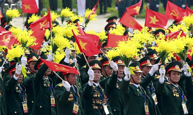 Veterans wave communist and Vietnamese national flags during a parade marking Vietnam's 70th National Day at Ba Dinh square in Hanoi, Vietnam September 2, 2015. (Photo by Reuters/Kham)