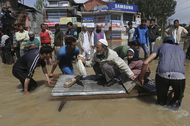 Kashmiri men use a makeshift raft to evacuate an elderly man and his grand daughter from a flooded neighborhood in Srinagar, India, Sunday, September 7, 2014. (Photo by Dar Yasin/AP Photo)