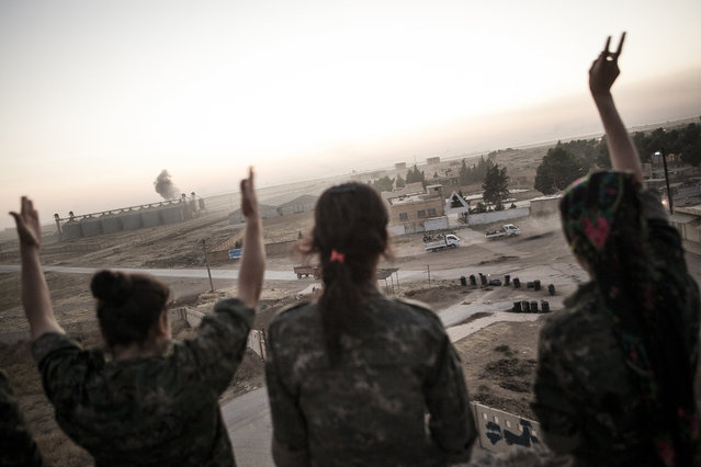 YPJ soldiers cheer and hold up the peace sign at the sight of Sinjar refugees in trucks being rescued and delivered to safety in Til Kocer, Syria, August 9, 2014. On the desolate Syrian-Kurdistan border live many YPG / YPJ soldiers, who are staked out at  makeshift posts to fend of IS attacks and protect the border. (Photo by Erin Trieb/NBC News)